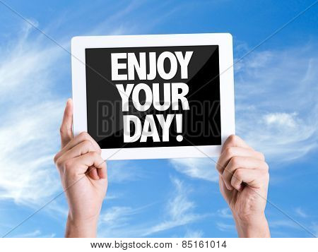 Tablet pc with text Enjoy Your Day with sky background
