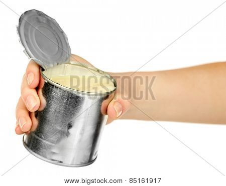 Female hand holding tin can of condensed milk isolated on white