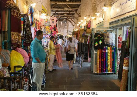 DOHA, QATAR - MARCH 8, 2015: Shopkeepers and shoppers in the textile section of the Souq Waqif arcade, a major tourist attraction,