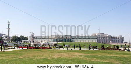 DOHA, QATAR - MARCH 8, 2015: The Emiri Diwan, or palace, the ruler's administrative building in Doha, Qatar, from the Souq Waqif Park, with laborers working in the foreground.
