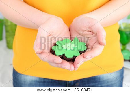 Woman holding cookie in shape of clover leaf for St Patrick Day close up