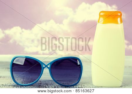 Bottle of suntan cream with sunglasses on table Bottle with suntan cream on table isolated on white