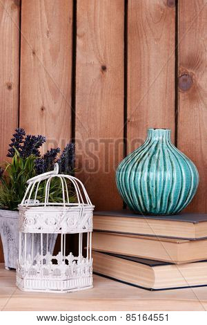 Interior design with decorative vase, cage, plant and stack of books on tabletop on wooden planks background