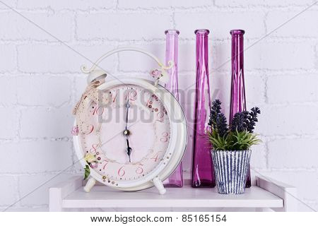 Interior design on tabletop with alarm clock, plant and decorative vases on white brick wall background