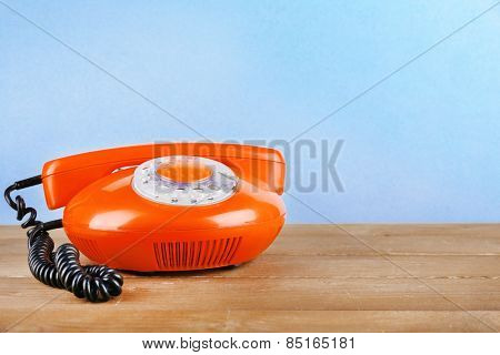 Retro telephone set on wooden table on light background