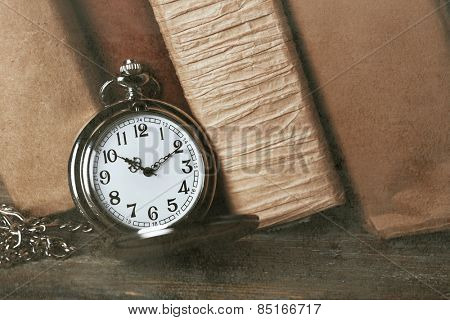 Silver pocket clock on books background
