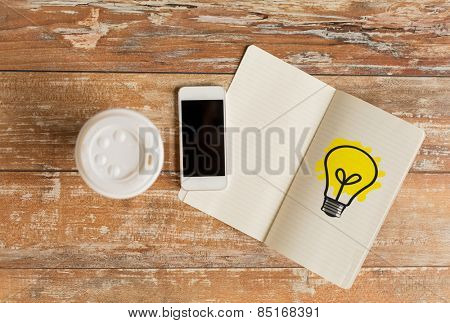 business idea, education, objects and technology concept - close up of coffee paper cup, smartphone and lighting bulb drawing in notebook on table