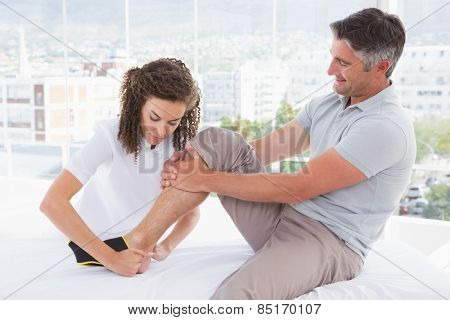 Doctor putting ankle brace to her patient in medical office