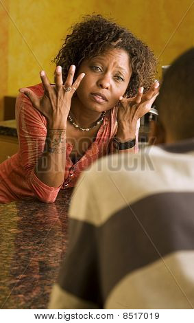 African-american Female And Male Talk In Kitchen