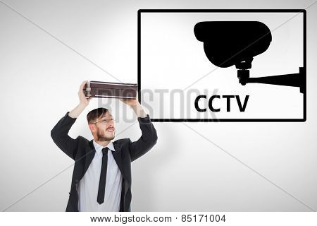Geeky businessman holding briefcase over head against cctv