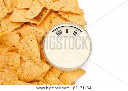 weighing scales against nachos placed around a bowl of dip
