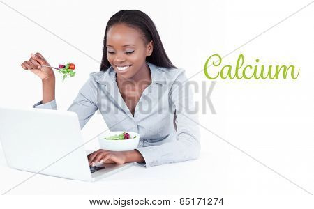 The word calcium against young businesswoman working with a notebook while eating a salad