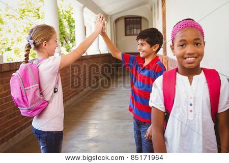 Portrait of smiling schoolgirl with friends high fiving in background at school corridor