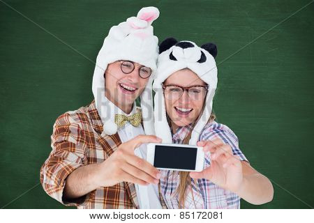 Geeky hipster couple taking selfie with smart phone against green chalkboard