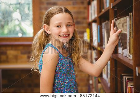Portrait of cute little girl selecting book in the library