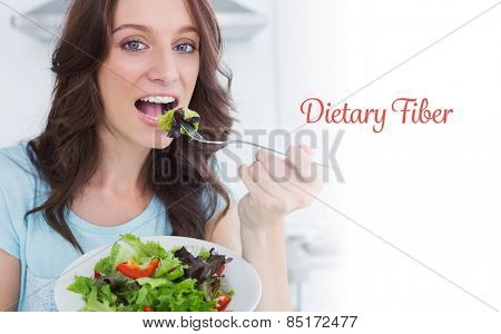The word dietary fiber against brunette eating healthy salad