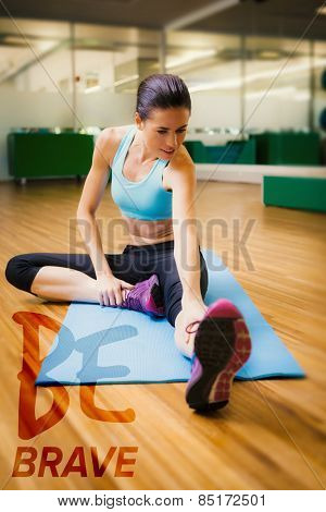 Fit brunette warming up in fitness studio against be brave