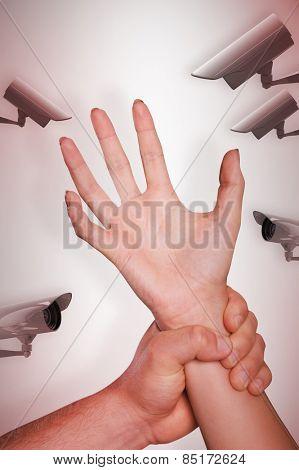 Male hand grabbing female wrist against cctv camera
