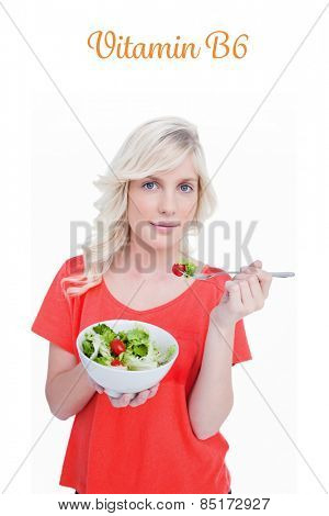The word vitamin b6 against young blonde woman eating a vegetable salad