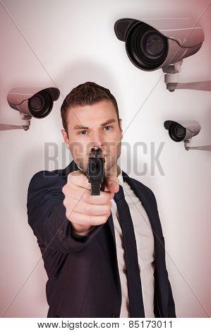 Serious businessman pointing a gun against cctv camera