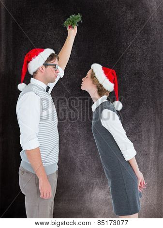 Geeky hipster kissing under mistletoe against black background
