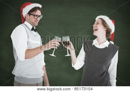 Happy geeky hipster couple drinking red wine against green chalkboard