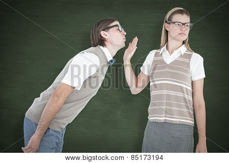 Geeky hipster making a stop sign to her boyfriend against green chalkboard