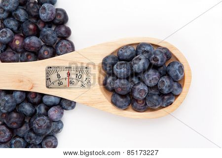 weighing scales against wooden spoon with blueberrry