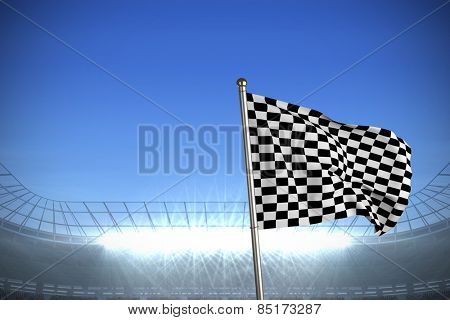 Checkered flag against large football stadium under bright blue sky