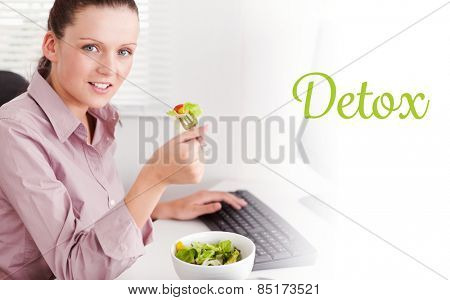 The word detox against businesswoman in office eating salad