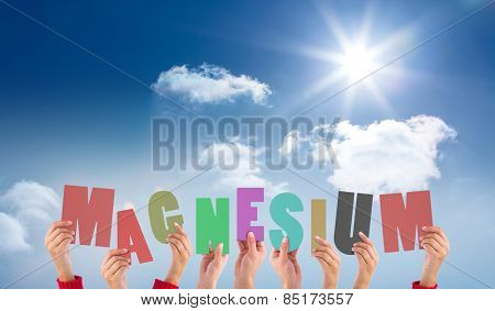 Hands holding up magnesium against bright blue sky with clouds