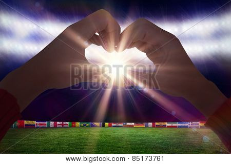 Woman making heart shape with hands against football pitch with world cup flags