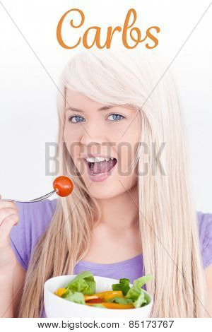 The word carbs against gorgeous smiling woman eating her salad