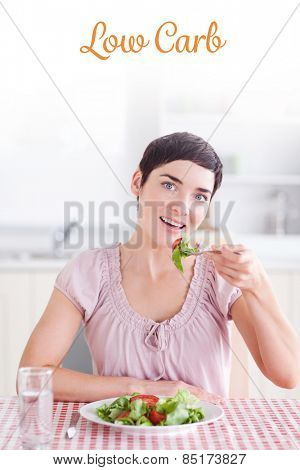 The word low carb against cheerful brunette woman eating salad