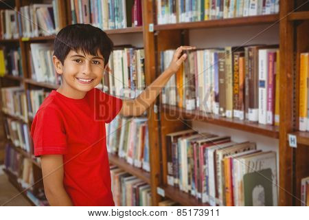 Portrait of cute little boy selecting book in the library