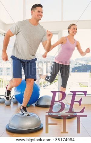 Couple doing step aerobics in fitness studio against be fit