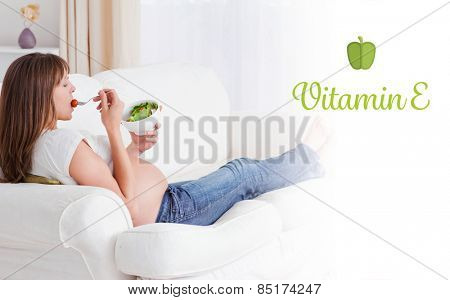 The word vitamin e against pretty pregnant woman eating a salad while lying on a sofa