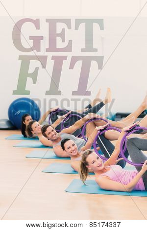 Sporty people with exercising rings in fitness studio against get fit