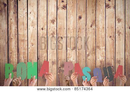 Hands holding up bona pasqua against wooden planks