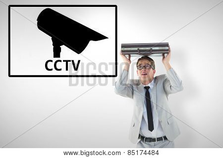 Handsome businessman sheltering with briefcase against cctv