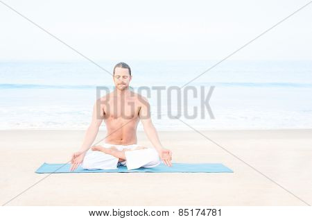 Fit man meditating on the beach