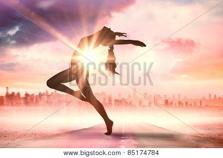 Side view of a sporty young woman stretching against sun shining over city