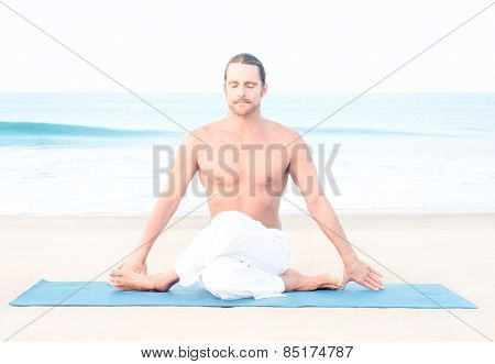 Fit man performing asana on the beach