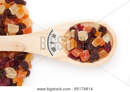 weighing scales against wooden spoon with dried fruit