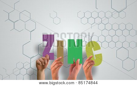 Hands holding up zinc against chemical structure in grey and white