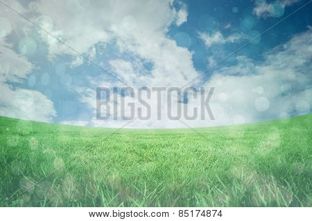 Blue abstract light spot design against green field under blue sky