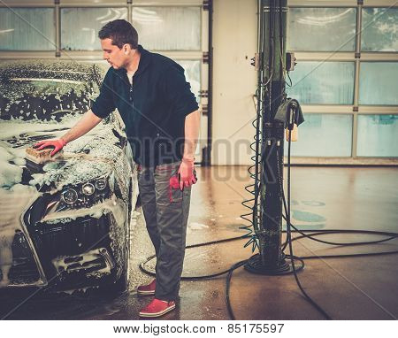 Man worker washing luxury car with sponge on a car wash