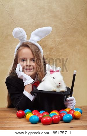Young magician after successfully conjuring an easter rabbit - sitting with satisfaction