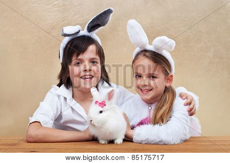 Kids with bunny ears holding their favorite pet - a white rabbit