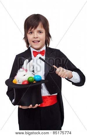 Young magician performing an easter trick - pulling a white rabbit and colorful eggs from the hat